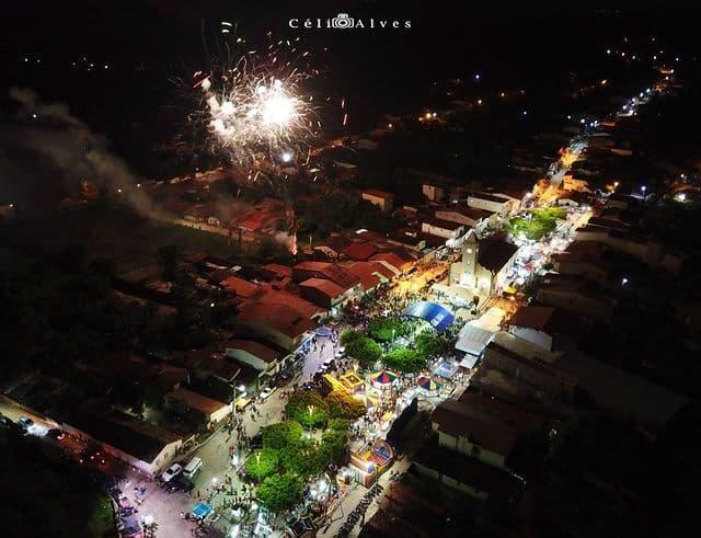 Fotografia tirada com drone do alto da praça matriz de Canaan em Trairi, pegando as casas, as árvores, a igreja, os brinquedos do parque de diversões, e um grande número de pessoas na praça. No alto, fogos de artifício.